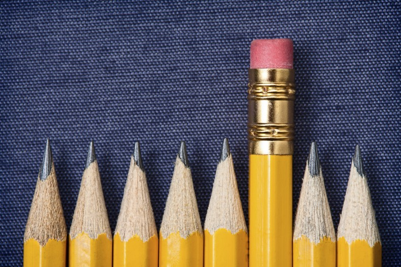 Standing out from the crowd concept. Yellow pencils and one with rubber eraser