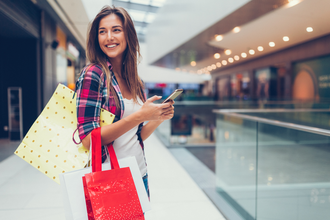 Happy girl with shopping bags texting on smartphone