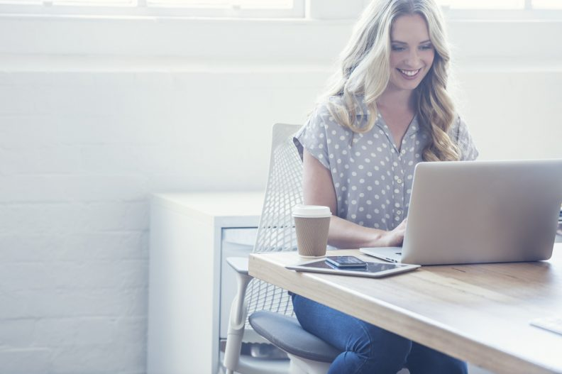 Attractive woman working on a laptop computer. She is casually dressed  with long blonde hair. She looks relaxed with a cup of coffee and she is probably surfing the internet. She could be a business woman working at home or in an office. Shot is back lit with copy space. There is a digital tablet and mobile phone on the table